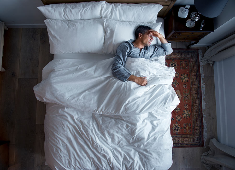 man-on-bed-with-a-headache-A2WGP74